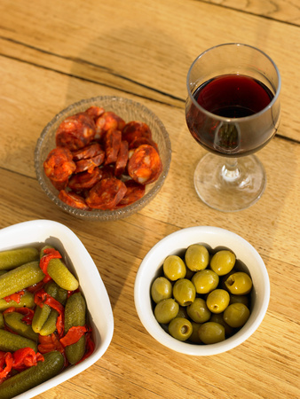 Glass of red wine and olives on table
