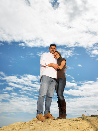 Couple embracing on hilltop Stock Photo