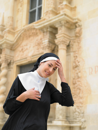 Nun smiling in front of ornate doorway Stock Photo