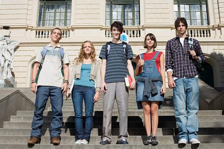 Tieners die op de trappen van de universiteit staan Stockfoto