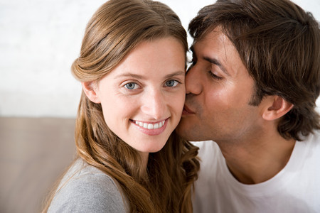 Man kissing a woman on the cheek Stock Photo
