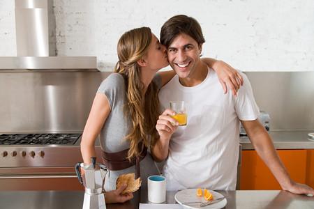 Woman kissing man on the cheek Stock Photo