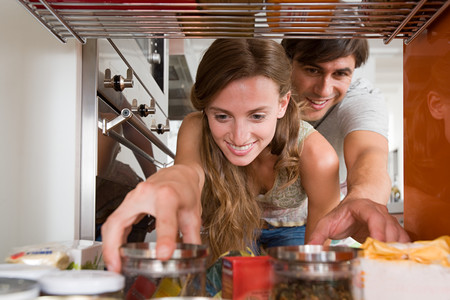 A couple reaching for jars of food