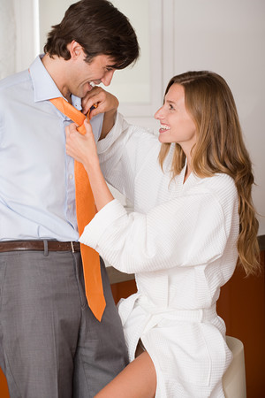 A woman tying a mans tie