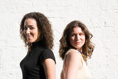 Two women standing back to back Фото со стока