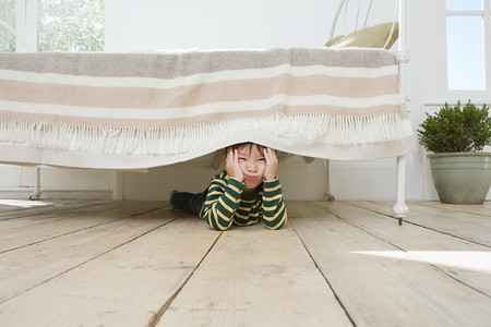 Boy hiding under a bed Фото со стока