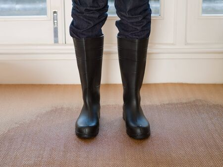Person wearing rubber boots on a wet carpet Imagens - 129131422