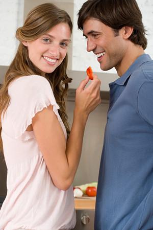 A woman feeding a man vegetables