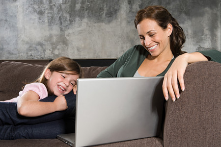 A mother and daughter looking at a laptop