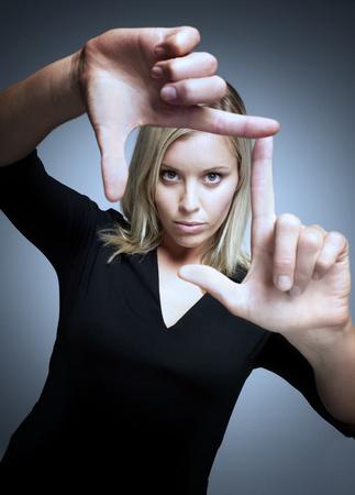 Woman loking through fingers Stockfoto