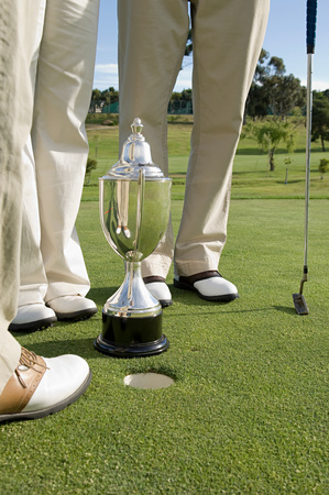 Golfers legs and a trophy 写真素材