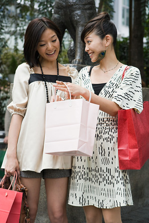 A woman showing her friend her shopping Stok Fotoğraf