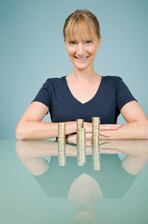 Woman with stacks of coins Stok Fotoğraf