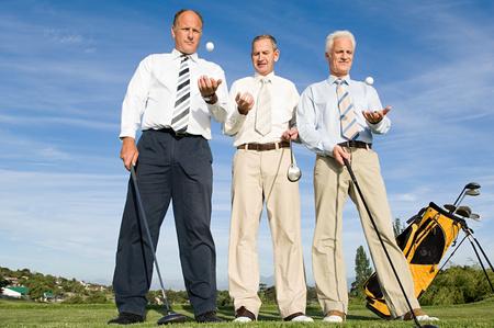 businessmen throwing golf balls