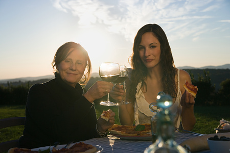 Mother and daughter toasting with red wine Stock Photo