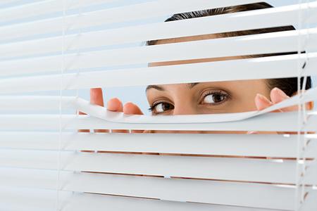 Mujer mirando a través de persianas