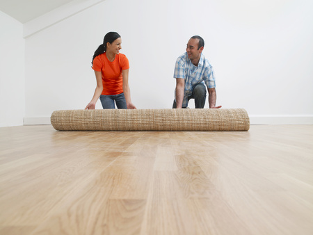 A couple rolling out a rug
