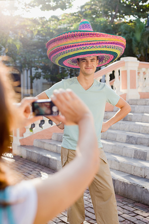 Woman photographing man wearing sombreros
