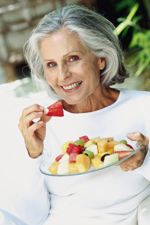 Ageing woman eating outdoors