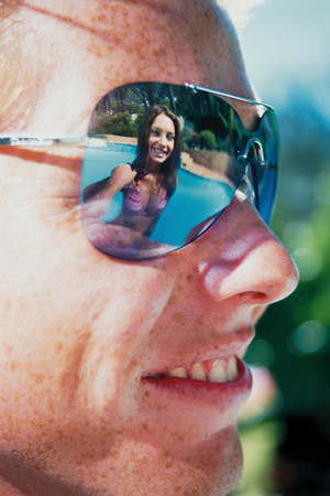 Young woman reflected in sunglasses