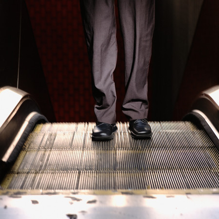 Businessman on escalator Reklamní fotografie
