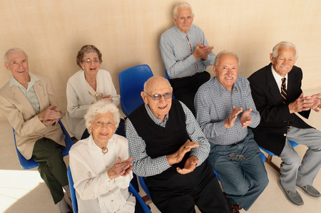 Elderly people looking up applauding Stock Photo