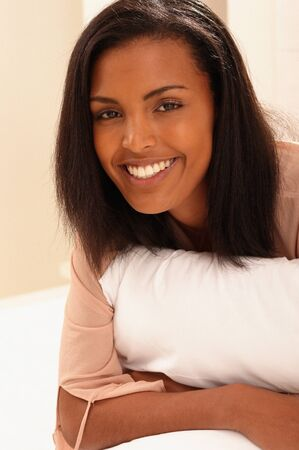 Smiling young woman with pillow