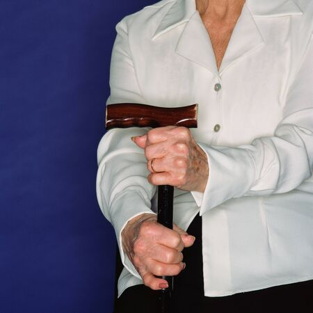 Elderly woman holding a walking stick