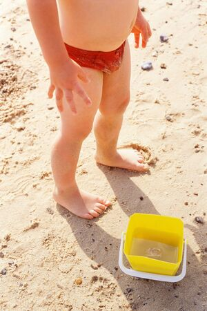 Child standing by bucket on the beach