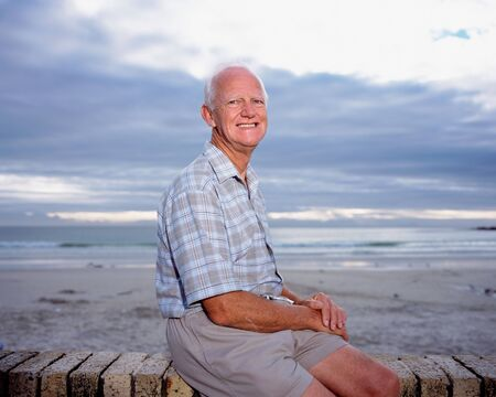 A mature man sitting by the sea
