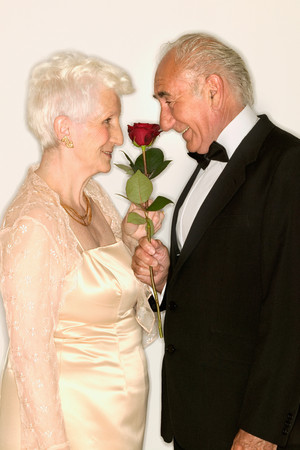 Senior couple sniffing rose Imagens