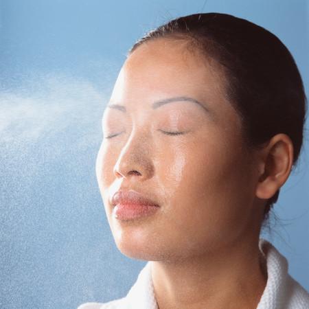 Pulverización de agua en la cara de la mujer Foto de archivo