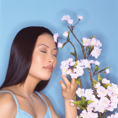 Young woman sniffing blossom