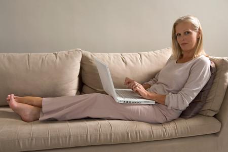 Mujer, en, sofá, con, computadora de computadora portátil