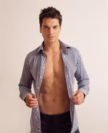 Man putting on a shirt