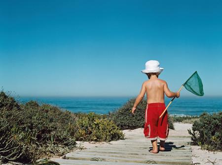 Boy walking to beach with a fishing net
