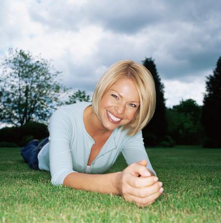 Blond woman lying on grass