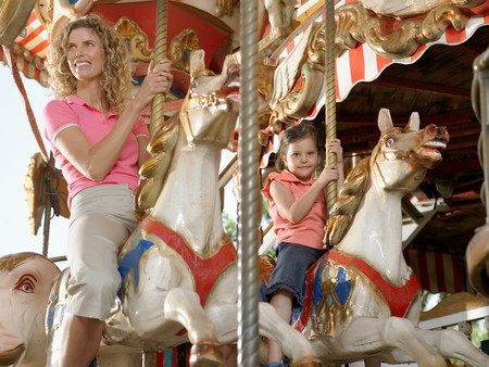 Mother and daughter on carousel 免版税图像