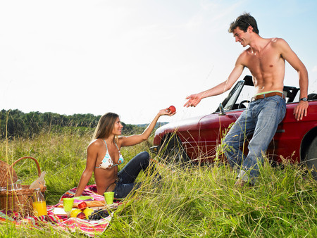Couple Having A Picnic In A Field Stock Photo