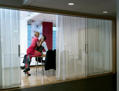 Woman Seducing Man In Board Room Stock Photo