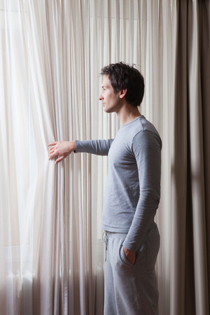 Man In Pyjama, Looking Out Of Window Stock Photo