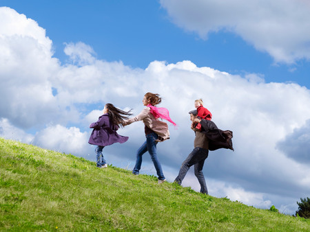 Family Of Four Walking Up Windy Hill