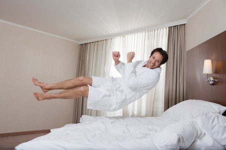 Businessman In Bathrobe Jumping On Bed