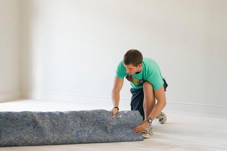 Man Unrolling Under Carpet Banque d'images - 117920437