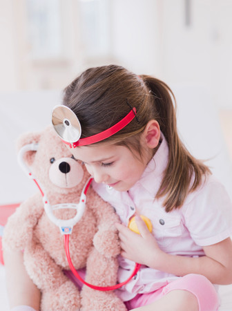 Girl In Toy Medic Attire And Teddy Bear Stock Photo