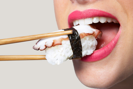 Woman Putting Sushi In Mouth