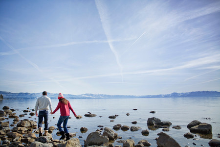 Couple Walking On Rocks Near Lake