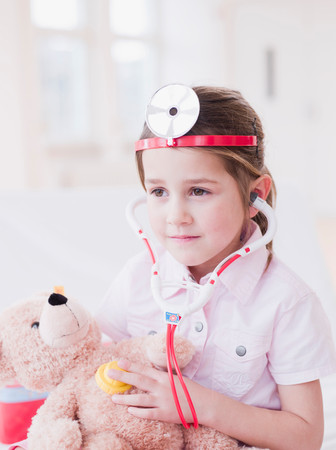 Girl In Toy Medic Attire And Teddy Bear