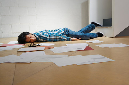 Young Man Lying On Office Floor Imagens