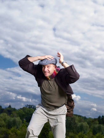 Man Holding Onto Hat In Wind
